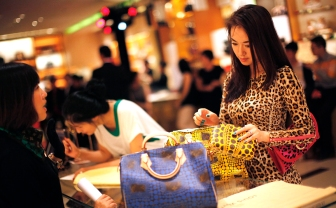 A woman shops in a Louis Vuitton store during Vogue's 4th Fashion's Night Out: Shopping Night with Celebrities in downtown Shanghai September 7, 2012. Louis Vuitton is courting China's wealthy with one-of-a-kind shoes and bags it is branding as unique works of art to reclaim its exclusive cachet in the luxury market. REUTERS/ Carlos Barria (CHINA - Tags: FASHION BUSINESS SOCIETY WEALTH)